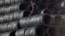 A labourer walks on coils of steel wire at a steel market in Shenyang, Liaoning province, China, in this Feb. 9, 2012 file photo. (SHENG LI/REUTERS)