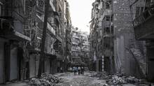 In this Saturday, Oct. 27, 2012 photo, Syrian residents walk on a street among the debris of buildings damaged by heavy shelling in the southeast of Aleppo City. (Narciso Contreras/AP)