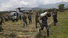 Nepalese soldiers unload relief material brought in an Indian air force helicopter for victims of Saturday's earthquake at Trishuli Bazar in Nepal, Monday, April 27, 2015. (Altaf Qadri/Associated Press)