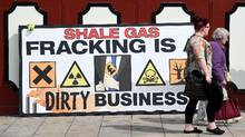 This file photo taken on June 24, 2015 shows people walking past an anti-fracking banner outside Lancashire County Hall in Preston, northwest England, on June 23, 2015. On Oct. 6, 2016, Britain approved a shale gas fracking project in the north of England, overruling a local council's decision to prevent the controversial scheme which is also opposed by environmentalists. (PAUL ELLIS/AFP/Getty Images)