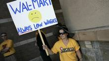 Diana Huffman holds a sign in support of striking Wal-Mart workers outside a Wal-Mart store in Pico Rivera, Calif., Oct. 4, 2012. Some Wal-Mart workers have planned to walk off the job on Black Friday, the busy shopping day right after American Thanksgiving. (JONATHAN ALCORN/REUTERS)