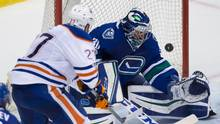 Edmonton Oilers' Milan Lucic puts a shot over the net behind Vancouver Canucks goalie Ryan Miller during second period NHL hockey action in Vancouver, B.C., on April 8, 2017. (DARRYL DYCK/THE CANADIAN PRESS)