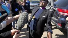 Archbishop Desmond Tutu speaks to reporters after viewing Alberta's oil sands from a helicopter. Tutu flew over the oil sands after giving the keynote address at the conference, As Long as the Rivers Flow: Coming Back to the Treaty Relationship in Our Time, in Fort McMurray, Alberta on Saturday May 31, 2014. (JASON FRANSON/THE CANADIAN PRESS)