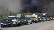 A convoy of evacuees drives south as flames and smoke rises along the highway near near Fort McMurray, Alberta on May 6, 2016. (COLE BURSTON//AFP/Getty Images)