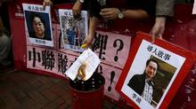 A demonstrator burns a letter next to pictures of missing Causeway Bay Books staff members in Hong Kong earlier this month. (Tyrone Siu/REUTERS)