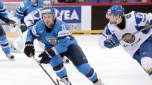 Kazakhstan's Konstantin Romanov, right, follows Finland's Leo Komarov during the Group H game Kazakhstan vs Finland in the 2012 IIHF Ice Hockey World Championships in Helsinki, Finland, on Monday May 14, 2012. (Heikki Saukkomaa/THE CANADIAN PRESS)