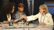 "This image released by ABC shows, Oprah Winfrey, left, grasping hands with Barbara Walters, right, as co-host Sherri Shepherd looks on during a taping of Walters' final co-host appearance on ""The View, "" Thursday, May 15, 2014 in New York. (IDA MAE ASTUTE/ASSOCIATED PRESS)"