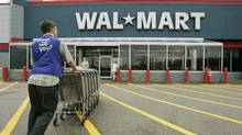 A Wal-Mart employee pushes a line of shopping carts toward the entrance of a Wal-Mart store, in Walpole, Mass., in this file photo. (Steven Senne/Steven Senne/AP)
