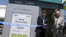 Former Toronto mayor David Miller, right, at the corner of Reese St. and Queen's Quay and Luc Sabbatini, president of Astral Media Outdoor, introduce the city's first automated public toilet. (Peter Power/The Globe and Mail)