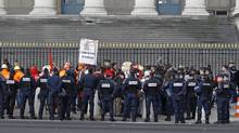 Riot policemen surround demonstrating workers from Arcelor Mittal in front of the National Assembly in Paris, Nov. 28, 2012. (Remy de la Mauviniere/AP)