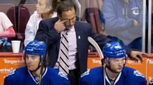 Vancouver Canucks' head coach John Tortorella, top, wipes his eye while standing behind players David Booth, left, and Nicklas Jensen, of Denmark, during third period NHL hockey action against the Calgary Flames in Vancouver, B.C., on Sunday April 13, 2014. (DARRYL DYCK/THE CANADIAN PRESS)
