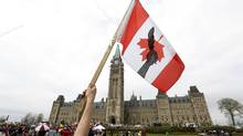 "A First Nations protester holds a flag during the ""National Day of Resistance"" protest on Parliament Hill in Ottawa May 14, 2014. (CHRIS WATTIE/REUTERS)"