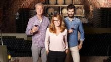 Portrait of multigenerational winery owner family standing at wine cellar. Senior winemaker and young sommelier standing at background and holding in hands a glass of red wine while middle age businesswoman looking at camera and smiling. Small business. (Szepy/Getty Images/iStockphoto)