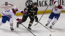 Anaheim Ducks center Nick Bonino, centre, dives for the puck against Montreal Canadiens left wing Travis Moen, left, and defenseman Josh Gorges during the first period of an NHL hockey game, Wednesday, in Anaheim, (Ringo H.W. Chiu/AP)