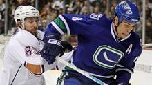 Edmonton Oiler Sam Gagner, left, and Vancouver Canuck Willie Mitchell. (DARRYL DYCK)