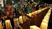 Pakistani workers of political party Muttahida Qaumi Movement 'MQM', light candles during a protest to condemn the killing of foreign tourists by militants, in Karachi, Pakistan, Sunday, June 23, 2013. Islamic militants wearing police uniforms shot to death many foreign tourists and one Pakistani before dawn as they were visiting one of the world's highest mountains in a remote area of northern Pakistan that has been largely peaceful, officials said. (Fareed Khan/AP)