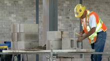 A mason at the new Bedford High School project in Bedford, N.S., works with a concrete brick using Halifax-based CarbonCure Technologies Inc.'s green technology. (CarbonCure)