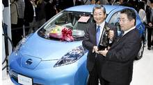 "Toshiyuki Shiga, COO of Nissan, receives the trophy for the ""Car of the Year Japan"" for Nissan's electric vehicle Leaf at the Tokyo Motor Show on December 3, 2011. (JIJI PRESS/JIJI PRESS/AFP/Getty Images)"