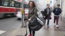 Madam Justice Mara Greene, the only female hockey-playing judge among a roster of about two dozen judges at Toronto's Old City Hall, walks to work after an early morning hockey practice in Toronto, Feb. 22, 2017. (MICHELLE SIU/NYT)