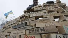 A Pro-European Union activists builds a symbolic fence using wooden bricks with names of Ukrainian cities during a rally in Independence Square in Kiev on Dec. 16, 2013. (Dmitry Lovetsky/AP)