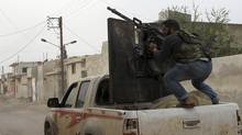 A member of the Free Syrian Army fires from a heavy machine gun towards pro-government forces in Salqin city in Idlib October 22, 2012. (ASMAA WAGUIH/REUTERS)