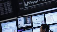 A trader looks at a TV screen showing news on Italy's 5-Star Movement leader and comedian Beppe Grillo, in front of the German share price index DAX board at the German stock exchange in Frankfurt February 26, 2013. (Lisi Niesner/Reuters)