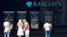 People use a line of Barclays cash dispensers in central London, June 28, 2012. (Reuters)