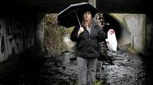 Jody Watson, chair of the Bowker Creek Initiative, holds a plastic bag filled with garbage she found walking through the creek. (Chad Hipolito/The Globe and Mail/Chad Hipolito/The Globe and Mail)