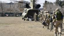 The last Canadians involved in the NATO training mission in Afghanistan board a U.S. Chinook helicopter as they leave the International Security Assistance Force (ISAF) headquarters in Kabul on March 12, 2014. (HANDOUT/Reuters)