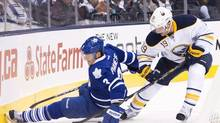 Toronto Maple Leafs defenceman Dion Phaneuf, left, gets tripped up by Buffalo Sabres forward Cody Hodgson, right, during first period NHL hockey action in Toronto on Monday, January 21, 2013. THE CANADIAN PRESS/Nathan Denette (Nathan Denette/THE CANADIAN PRESS)