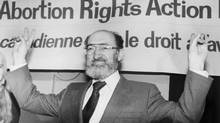 Henry Morgentaler, seen in Toronto in 1988, raises his arms in victory after the Supreme Court ruled the Criminal Code's abortion provision to be unconstitutional. On Wednesday, the Trudeau government tabled legislation to remove provision altogether. (Blaise Edwards/THE CANADIAN PRESS)