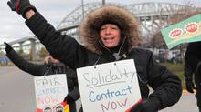 Pam Domenichini and fellow workers of the Blue Water Bridge picket at the bridge administration building, next to the span between Sarnia and Port Huron, Michigan on Monday, Nov. 21, 2016, in Sarnia, Ontario. (Dave Chidley/THE CANADIAN PRESS)
