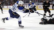 St. Louis Blues' Chris Stewart, left, shoots as Anaheim Ducks' Toni Lydman, background right, falls to the ice during the first period of an NHL hockey game in Anaheim, Calif., Sunday, March 10, 2013. (Associated Press)