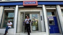 A customer leaves an Eurobank branch in central Athens Oct. 5, 2012. The National Bank of Greece has proposed a merger with Eurobank, its main domestic competitor. (JOHN KOLESIDIS/REUTERS)