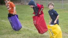 "Ben Quinnan, right, and two other students start a round of the ""messenger bag relay race"" during St. Charles Elementary School's annual ""ThinkStretch"" celebration, Friday, Sept. 12, 2014. Children permitted to play outdoors on their own or with friends are getting more physical activity than kids who are constantly supervised, a new Canadian study suggests. (Jeff Schrier/The Associated Press)"