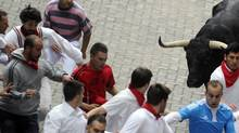 Man, left, wearing white with a beard, is pictured before falling down and being gored in the right thigh during the third running of the bulls at the San Fermin festival in Pamplona July 9, 2014. He has been identified as Bill Hillmann. (Eloy Alonso/Reuters)