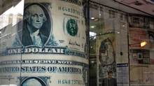 An Egyptian man stands next to a giant poster of U.S. dollars inside a currency exchange office in Cairo, Dec. 25, 2012. Bankers said a rush to American currency by residents has left banks and money changers short of dollars. (Khalil Hamra/AP)