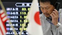 A Japanese foreign currency broker talks on the telephone (YURIKO NAKAO/Yuriko Nakao/Reuters)