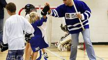 NHL players Marc Giordano, right, high fives a teammate as he plays ball hockey with members of the Foothills Minor Hockey Association after the NHLPA donated $50,000 in equipment to the association in High River, Alta., Tuesday, Sept. 3, 2013. (JEFF MCINTOSH/THE CANADIAN PRESS)