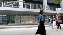 People pass by a Telus store in Toronto on June 3, 2012. (Michelle Siu For The Globe and Mail)