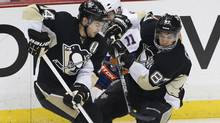 Pittsburgh Penguins' Sidney Crosby and Chris Kunitz squeeze out New York Islanders' Lubomir Visnovsky as they fight for the puck during the first period of Game 5 of their NHL Eastern Conference quarter-final hockey game in Pittsburgh, Pennsylvania May 9, 2013 (Reuters)