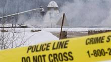 Smoke rises as police tape surrounds Babine Forest Products' mill in Burns Lake, B.C. Saturday, Jan. 21, 2012. (JONATHAN HAYWARD/THE CANADIAN PRESS)