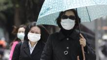 Pedestrians wearing medical masks walk on the street outside National Taiwan University Hospital in Taipei on April 26, 2013, after it was learned that a Taiwan businessman had contracted the H7N9 strain of bird flu while travelling in China. (PICHI CHUANG/REUTERS)