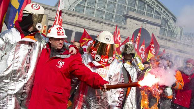 French union members light a flare during a demonstration outside an EU summit in Brussels on Thursday, March 14, 2013. Thousands of workers are converging on EU headquarters to demand an end to austerity measures. (Virginia Mayo/AP)