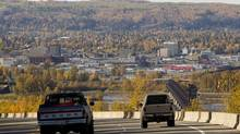 Pickup trucks are seen driving into Prince George, B.C., along Highway 16, on Oct. 8, 2012. (JONATHAN HAYWARD/THE CANADIAN PRESS)