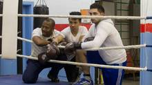 Montreal police officer Evens Guercy (left) watches training alongside 17- year old Alexandre Leng (centre) by the ring at Guercy's Hope Boxing Club in the St. Michel district of Montreal, March 19, 2012. (Christinne Muschi for The Globe and Mail/Christinne Muschi for The Globe and Mail)