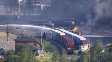 Firefighters douse rail containers in downtown Lac Mégantic, Que., on July 7, 2013, a day after a train carrying crude oil tankers derailed and burst into flames. (MOE DOIRON/THE GLOBE AND MAIL)