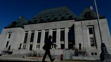 A pedestrian walks past the Supreme Court of Canada in Ottawa on Thursday, July 23, 2015. (Sean kilpatrick/THE CANADIAN PRESS)