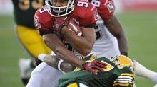 Calgary Stampeders' Jon Cornish is caught by Edmonton Eskimos' Julius Williams during their CFL game in Edmonton September 7, 2012. (DAN RIEDLHUBER/REUTERS)