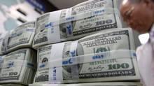 Stacks of $100 (U.S.) bills sit on a desk at a bank in South Korea.